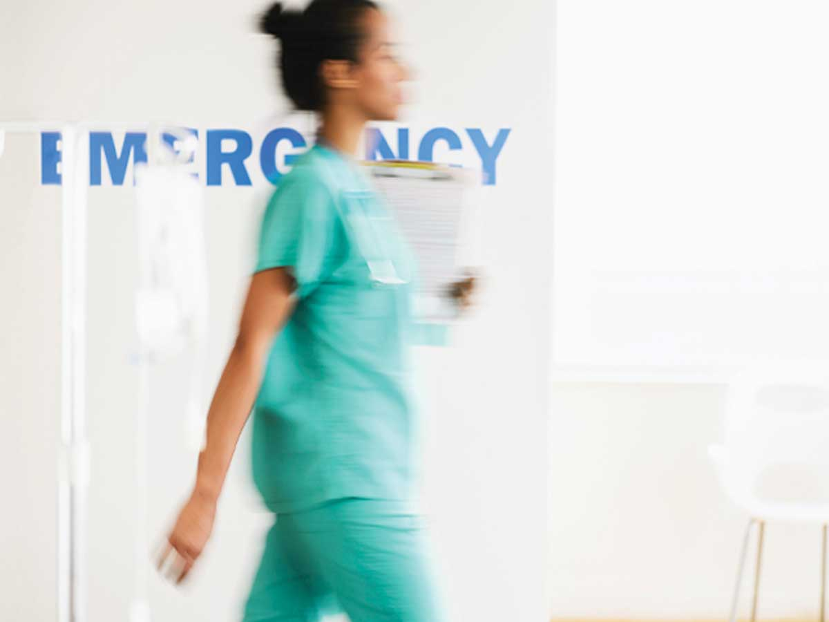 ER Staff member walking in front of Emergency sign