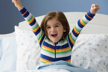 Young child stretching in bed after waking up