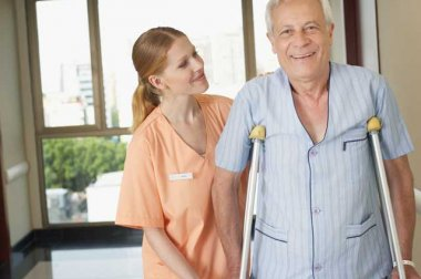 Older male patient with crutches helped by a nurse