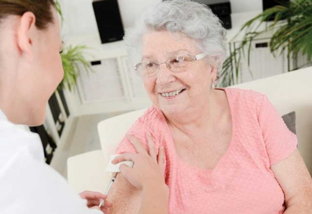 Older woman getting a shot by a health care provider