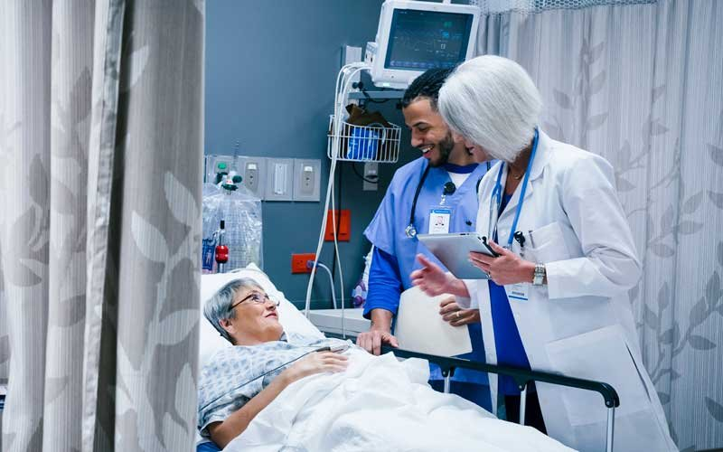 Two health care workers talking with a patient in an ER bed